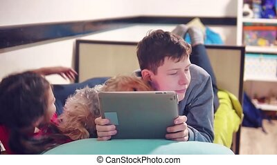 little boy and girl are playing and dog on the tablet lying...