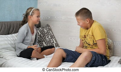 Little boy and girl are playing on the sofa