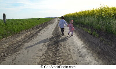 Little boy and girl are walking on path in field