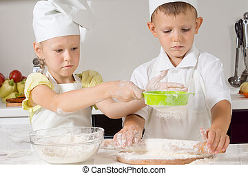 Little boy and girl baking in the kitchen