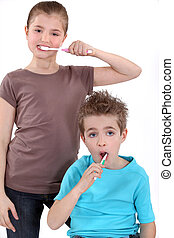 little boy and girl brushing their teeth