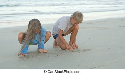 Little boy and girl draw on sand.