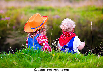 Little boy and girl dressed up as cowboy and cowgirl playing...