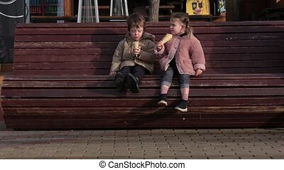 Little boy and girl eat delicious ice-cream in wafer cones sitting on brown wooden bench on city street in autumn evening