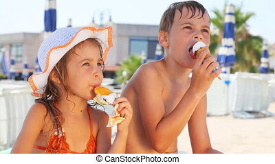 Little boy and girl eat ice cream on beach in hot summer