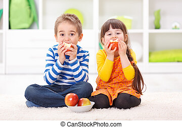 Little boy and girl eating apples