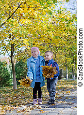 Little boy and girl gathering autumn leaves