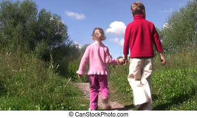 Little boy and girl go back on path in park. Summer day.