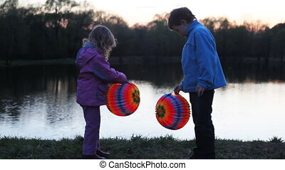 little boy and girl hold colorful ball from paper at night