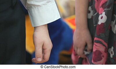 Little boy and girl holding hands in kindergarten