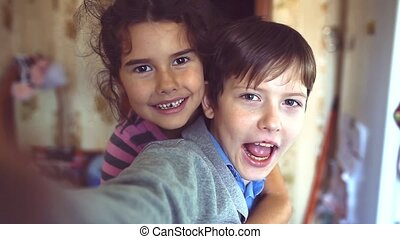 little boy and girl hugging do selfie. boy with a girl hugging children friendship concept. little cute boy and girl hugging playing on in lifestyle the room indoors
