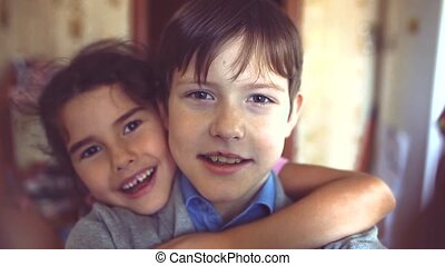 little boy and girl hugging do selfie. boy with a girl hugging children friendship concept. little cute boy and girl hugging playing on lifestyle in the room indoors