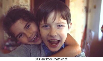 little boy and girl hugging do selfie. boy with a girl hugging children friendship concept. little cute boy and girl hugging playing lifestyle on in the room indoors