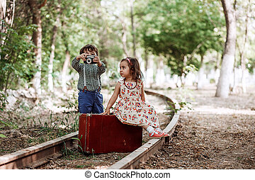 little boy and girl in vintage clothes with vintage suitcase and with vintage camera on abandoned railway