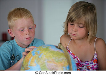 little boy and girl looking at a globe