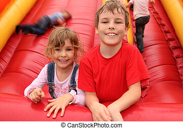 little boy and girl lying on red inflatable slide, smiling...