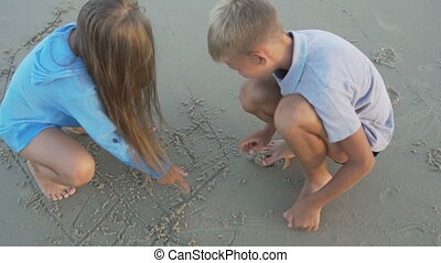 Little boy and girl of 8 - 10 years old draw on sand.