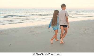 Little boy and girl of 8 - 10 years old walking along the beach