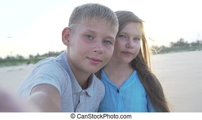 Little boy and girl of 8 - 10 years old making video selfie using smartphone.