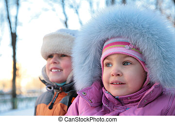 little boy and girl on street in winter