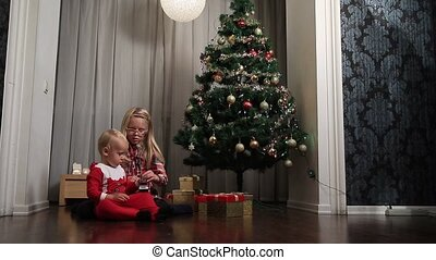 Little boy and girl opening presents on Christmas