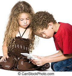 Little boy and girl playing console game - caucasian little...