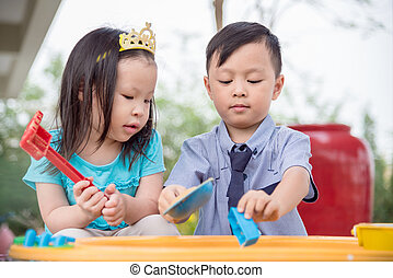 Little boy and girl playing sand in sandbox together