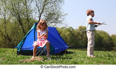 Little boy and girl plays near blue tent