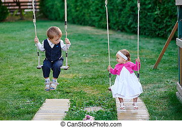 little boy and girl ride on a swing at the playground in the park