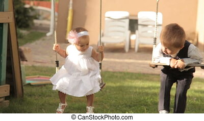 little boy and girl ride on the swing