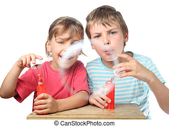 little boy and girl sit at table and blow bubbles isolated on white