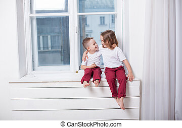 little boy and girl sit on the windowsill looking out the window
