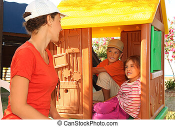 little boy and girl sitting in toy house at playground and looking on mother, sunny day