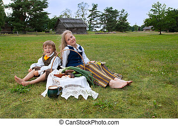 Little boy and girl sitting on a lawn in a national latvian clothes