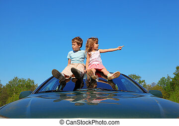 little boy and girl sitting on car roof on blue sky, looking to sides and showing by finger, wide angle