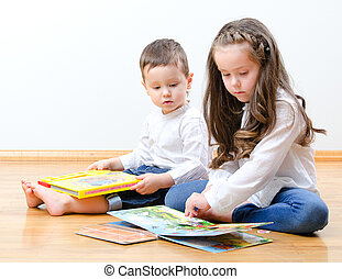 Little boy and girl sitting on the floor and reading a book