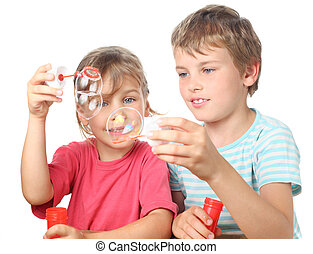 little boy and girl sitting, smiling and blowing bubbles isolated on white