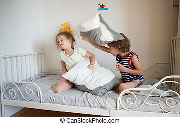 Little boy and girl staged a pillow fight on the bed in the bedroom.