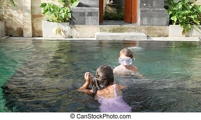 Little boy and girl swim underwater in swimming pool