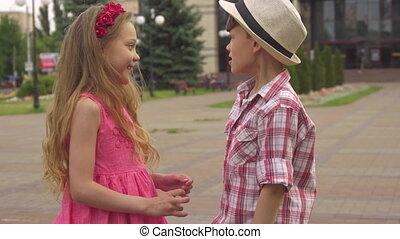 Little boy and girl talk outdoors