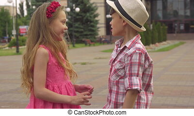 Little boy and girl talk outdoors