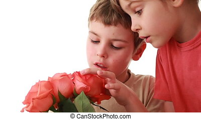 Little boy and girl touch beautiful pink roses in bouquet