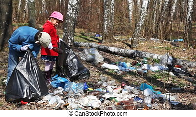 little boy and girl with black bags collect lot of garbage in park