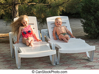 Little boy and girl with luxurious hair in lounge chair, on nature background