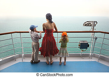 little boy and girl with mother standing on ship deck and looking at horizon