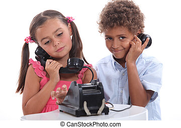 Little boy and girl with old fashioned telephone