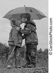 Little boy and girl with umbrella - Little boy kiss girl,...