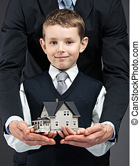 Little boy and hands keeping house model - Close up of...