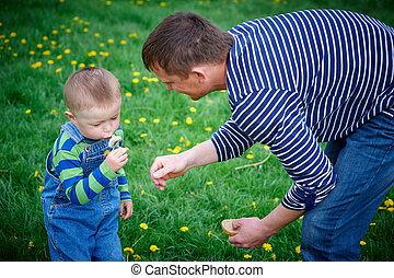 little boy and his father play with dandelions