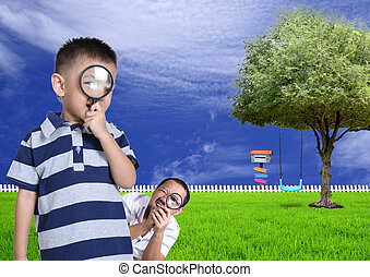 Little boy and his funny father with magnifying glass in the gar